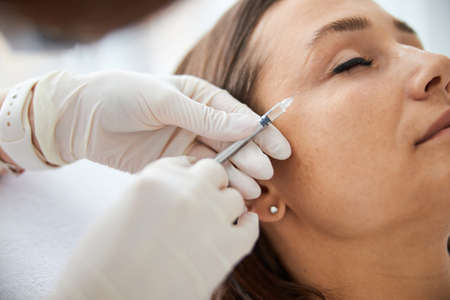 Dark-haired Caucasian woman undergoing a mesotherapy procedure