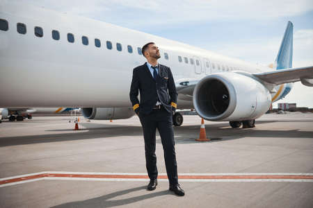 Pilot looking far away while standing on runway near plane
