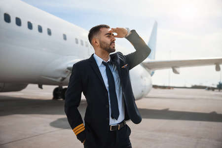 Male airplane pilot covering his eyes while watching ahead