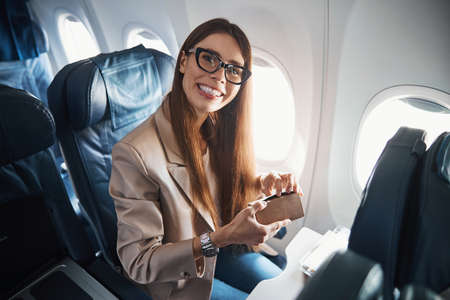 Happy lady sitting near plane window while holding box