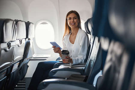 Contented female passenger of the airplane sitting alone Banco de Imagens
