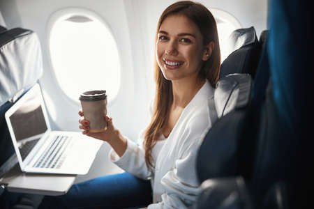 Female passenger with her favorite hot beverage during the flight