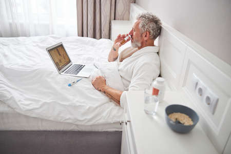 Bearded Caucasian male sitting on the bed while talking with doctor on video call Foto de archivo