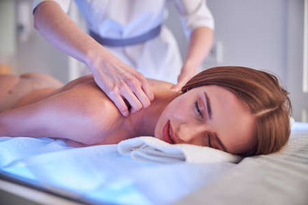 Gorgeous young lady relaxing at the spa complex in beauty clinic