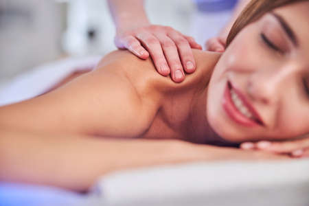 Happy cheerful elegant woman receiving professional treatment in spa center