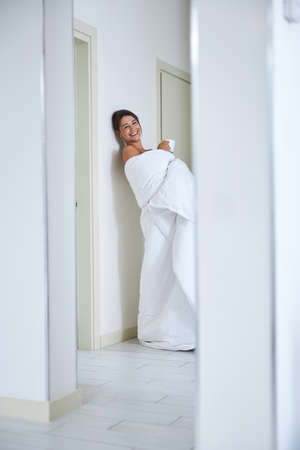 Pretty Caucasian lady covered in quilt while having fun in modern corridor in her flat Stock Photo