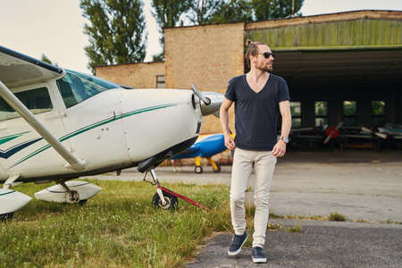 Handsome bearded man walking near private planes