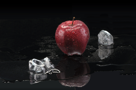 Apple and melting ice, still life photo feeling fresh and cold on black background