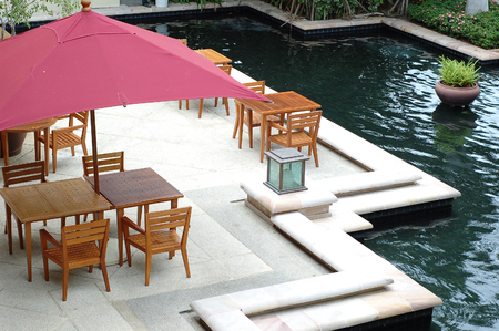 Out door restaurant with wood dining table near pool Stock Photo