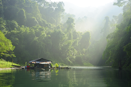 Cottage by water lake in green natural forest. Life near lake use a boat for travel and fishing. Lifestyle in Surat Thani - Chiew Larn Lake, Khao Sok National Park. Stock Photo