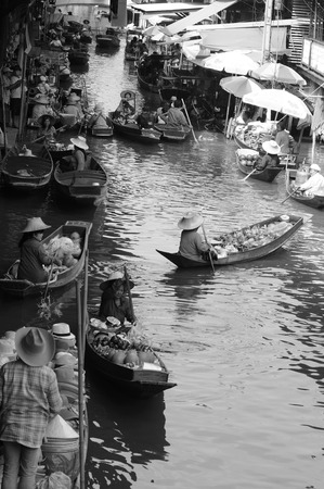 Ratchaburi, THAILAND - December 30, 2014: Damnoen Saduak Floating market in morning have seller paddle boat for sell local fruits, food, beverage and souvenir on canal. Black and white image.