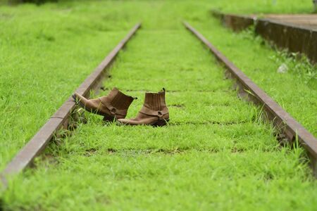 Side view, Retro brown boot are placed on the tracks. In the rainy season the old railway tracks are covered with green grass.