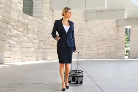 Business woman in business trip walking with wheel bag and holding a phone photo