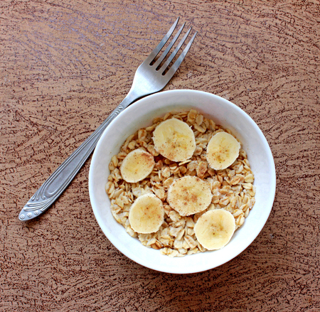 Oat flakes in a white bowl and fork on brown background