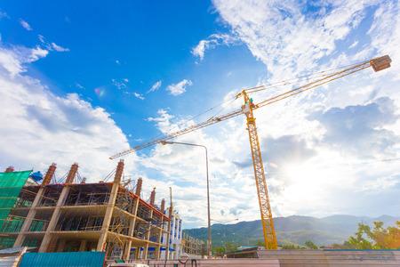 concrete commercial block: buildings under construction and cranes under a blue sky