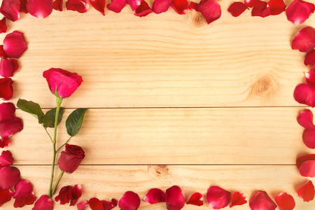 Frame shape made out of rose petals on wood background, Valentines Day, wedding day