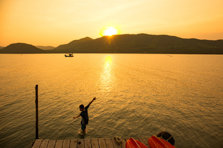 care about the health: The boy jumping in sae at early evening. Golden sunset.Summer time, active recreation. Healthy lifestyle and care about mental health, resting in privacy and peace.