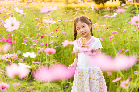 Cute little girl eating ice cream  in the field of pink flowers at sunlight Stock Photo