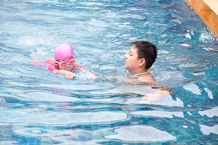 Smiling boy and little girl swimming in pool Stock Photo