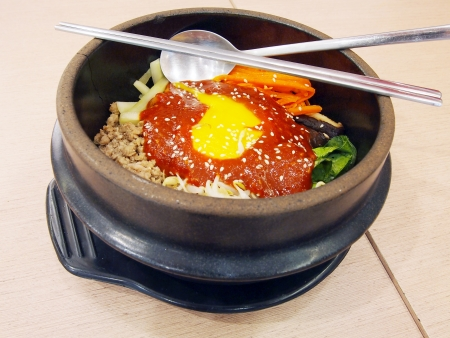 whie: bibimbap in a heated stone bowl, korean dish