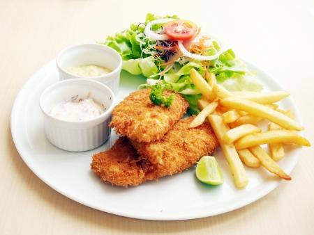 fish chips: El pescado frito con ensalada fresca y salsa como condimento