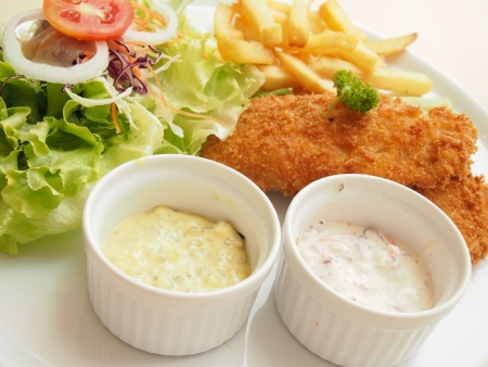 Fried fish with fresh salad and dipping sauce as condiments photo