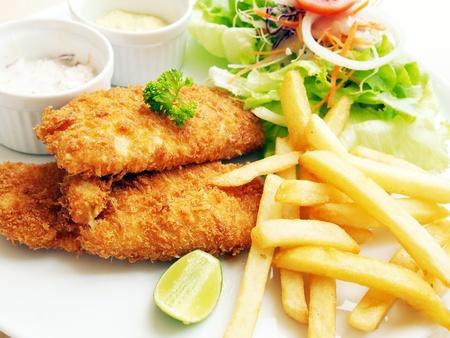 fish and chips: El pescado frito con ensalada fresca y salsa como condimento