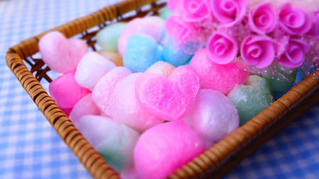 Sweet roses with rainbow decoration heart ball in a bamboo basket photo