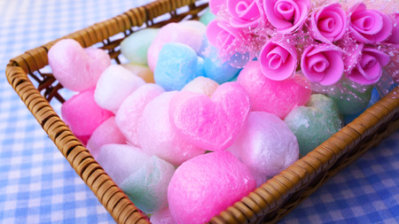 playtime: Sweet roses with rainbow decoration heart ball in a bamboo basket