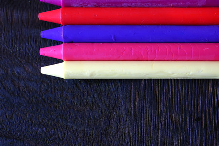 stationery needs: colorful Oil pastel crayons on a wooden  black table Stock Photo