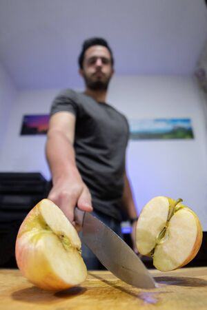 Self-portrait of a person cutting an apple with a large knife on a wooden table Фото со стока