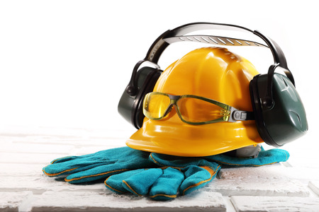 Yellow hard hat with headphones against noise, goggles and gloves on white bricks Archivio Fotografico
