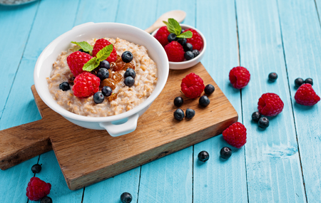 oatmeal: Oatmeal porridge with fresh berries on blue wooden background. Healthy breakfast breakfast for children, health and diet concept. Stock Photo