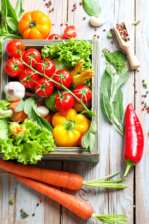 flavouring: Summer Vegetables set for cooking. Fresh farm vegetables and herbs on rustic background. Bio Organic food. Food background with copy space. Homemade Healthy Cooking concept. Vegetarian eating.