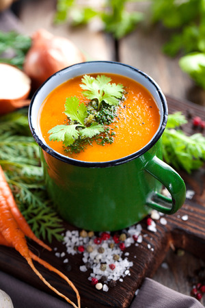 Vegetables cream soup in rustic metal pot with fresh organic ingredients and green. Healthy homemade food. vegeterian cooking Stock Photo