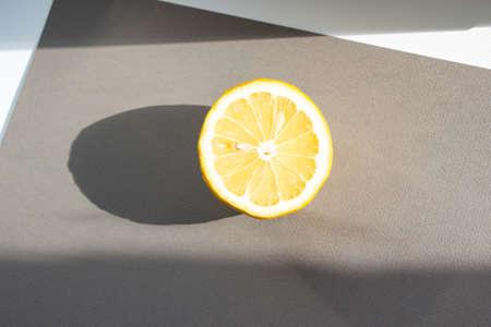 half of a whole lemon lies on a gray background. Sunlight feeds lemon Stock Photo