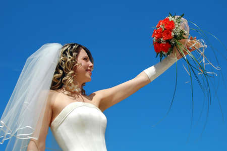 The happy bride with a bouquet of roses on a background of the sky