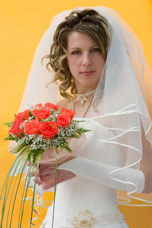 The bride with a bouquet of roses on a yellow background photo