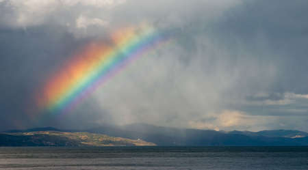rainbow clouds: A rainbow breaks through the storm clouds Stock Photo