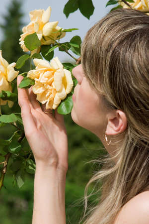 Woman smelling the yellow roses photo
