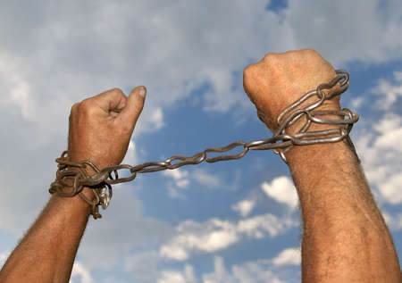 catena: Hands with chains around them on sky background