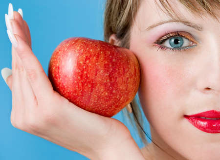 The woman with  appetizing apple on a blue background Stock Photo - 1124617
