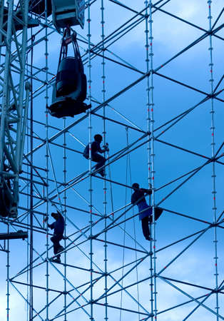 scaffold: Silhouettes of builders on a background of the sky