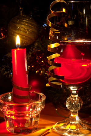 Christmas still-life. Glass of red wine and candle. photo