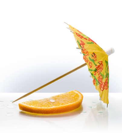 Fetta di arancia e di carta ombrello  Archivio Fotografico