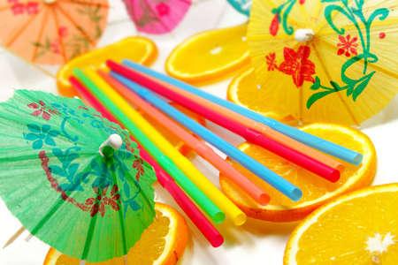 Straw, slices of  orange and decorative umbrellas photo