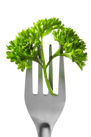 Close-up of a fork with parsley on white  photo