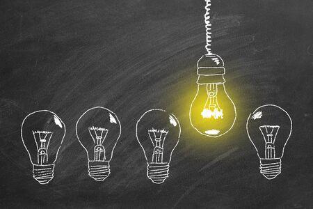 Row of light bulbs chalk drawing on  blackboard. Concept of idea. 版權商用圖片