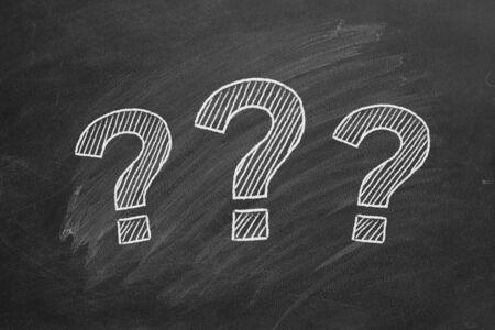 Three question marks drawn in chalk on a blackboard.