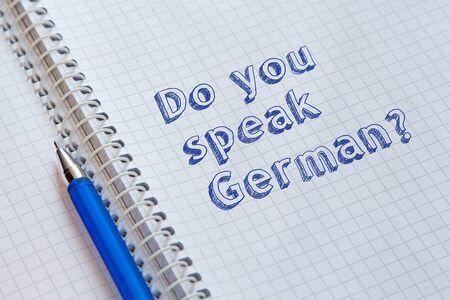 Do you speak German? Text handwritten on sheet of notebook